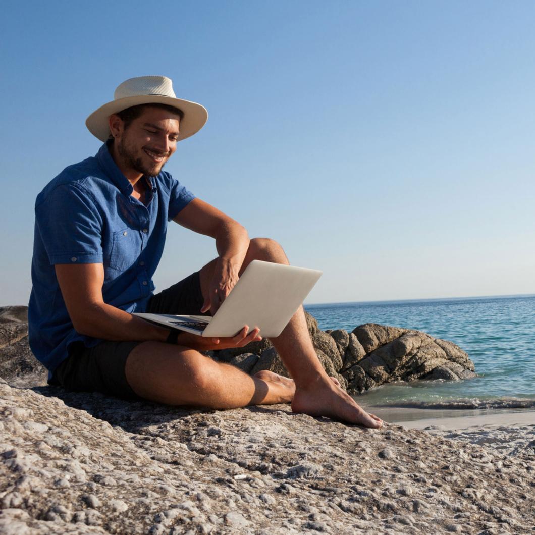 мужчина в шляпе на море с ноубтуком